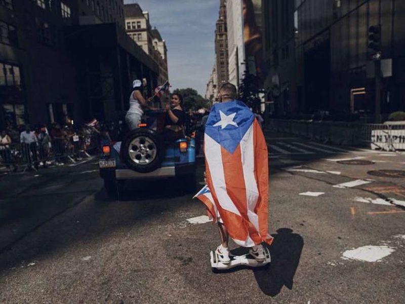 In this june 11, 2017 file photo, a man rolls on a hover-board along Fifth Avenue during the National Puerto Rican Day Parade in New York.