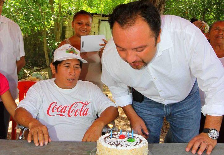 El diputado Francisco Torres Rivas sopla las velas del pastel que le regalaron vecinos de la colonia San Antonio Xluch. (Cortesía)