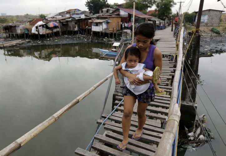 Una mujer carga  un bebé mientras cruza un puente en un barrio de Paranaque, al sur de Manila. (EFE)