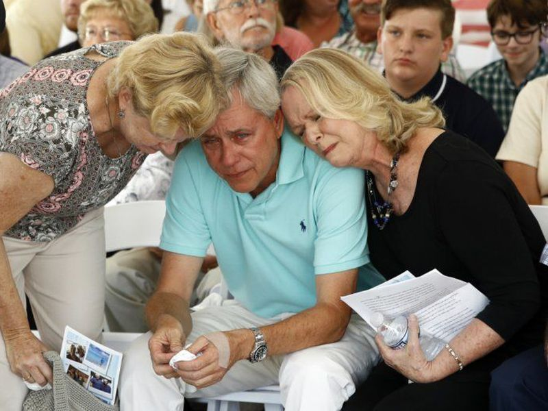 Carl Hiaasen, center, brother of Rob Hiaasen, one of the journalists killed in the shooting at The Capital Gazette newspaper offices, is consoled by his sisters Barb, left, and Judy during a memorial service, in Owings Mills, Md.