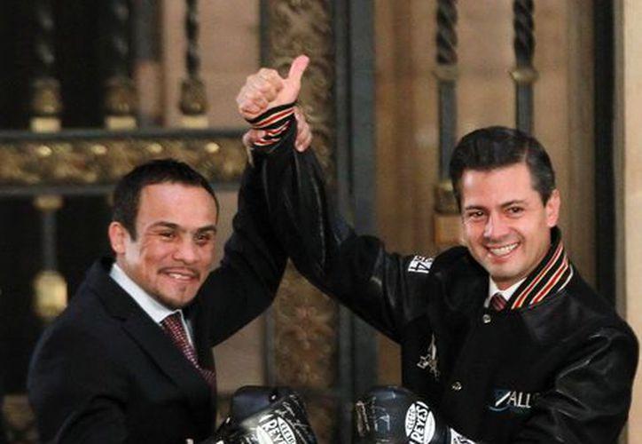 Peña Nieto aseguró que los guantes con que Márquez noqueó al filipino Manny Pacquiano, acreditan que sí se puede. (Notimex)