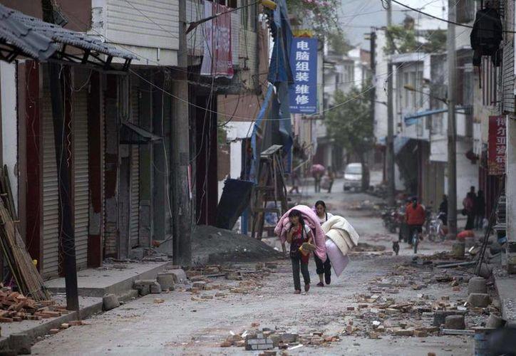 Personas caminan entre escombros en la villa de Gucheng, en el pueblo de Longmen. (Agencias)