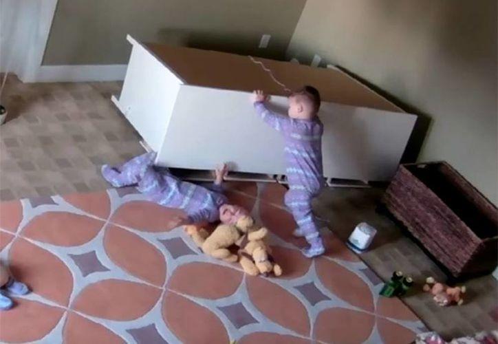 En el video se observa el momento en que uno de los gemelos intenta todo para poder ayudar a su hermano, al final, logra liberarlo del pesado mueble. (Captura de pantalla/Kayli Shoff/Youtube)