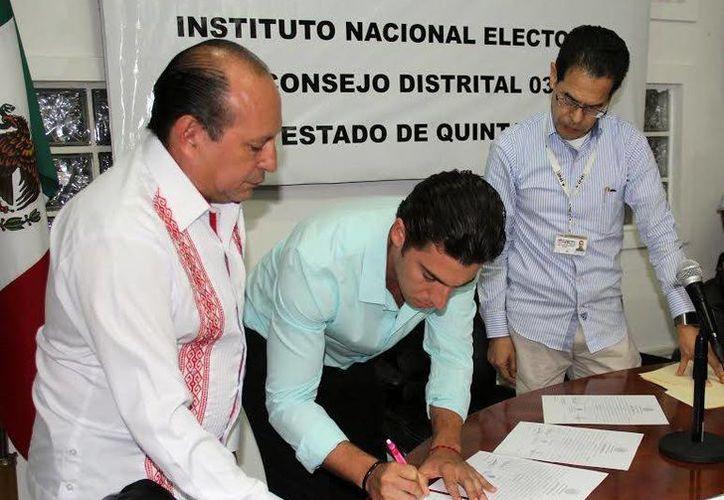 El ganador firmó el documento ante la autoridad del INE. (Francisco Naranjo/SIPSE)