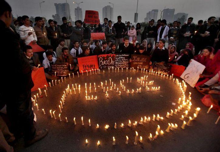 Estudiantes paquistaníes realizan una vigilia por las víctimas que murieron en un ataque talibán contra una escuela, en Islamabad, Pakistán. (Agencias)