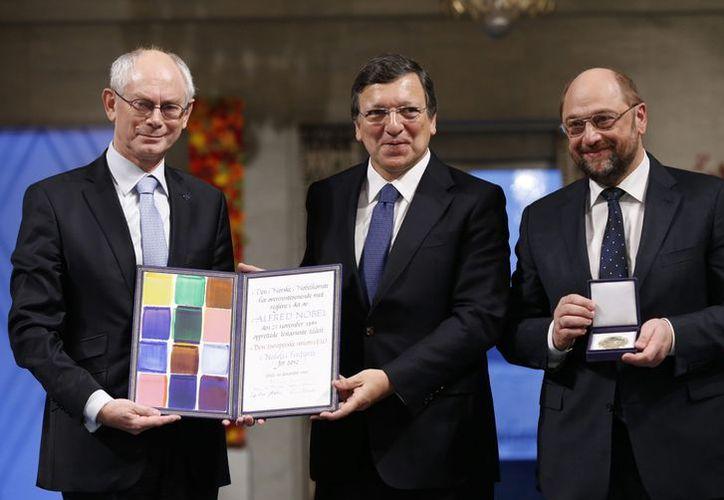 Desde la izquierda: , el presidente del Consejo Europeo, Herman Van Rompuy, el presidente de la Comisión Europea, José Manuel Barroso, y el presidente del Parlamento Europeo, Martin Schulz, con el diploma Nobel. (Agencias)