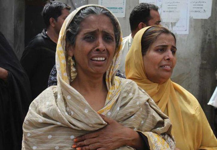 Residentes del barrio Lyari de Karachi, en Pakistán, ante las secuelas de un ataque contra transeúntes. (Agencias)
