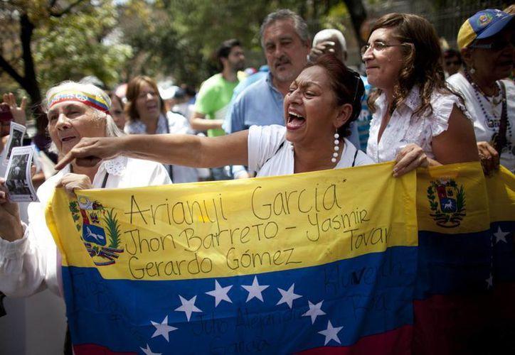 Mientras en varias ciudades se desarrollan intensas protestas, el presidente Maduro advirtió en radio y televisión que un grupo de paramilitares está intentando generar violencia en tres estados fronterizos. (AP)