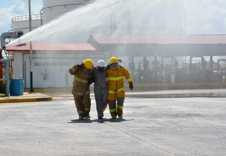 En el incendio de una refinería de Pemex se registraron ocho trabajadores lesionados; ninguno de gravedad. Imagen de contexto de dos trabajadores heridos. (Archivo/Notimex
