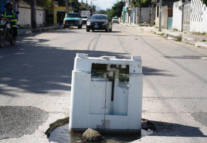Una lavadora fue colocada por vecinos de la colonia Colosio para señalizar un bache. (Octavio Martínez/SIPSE)