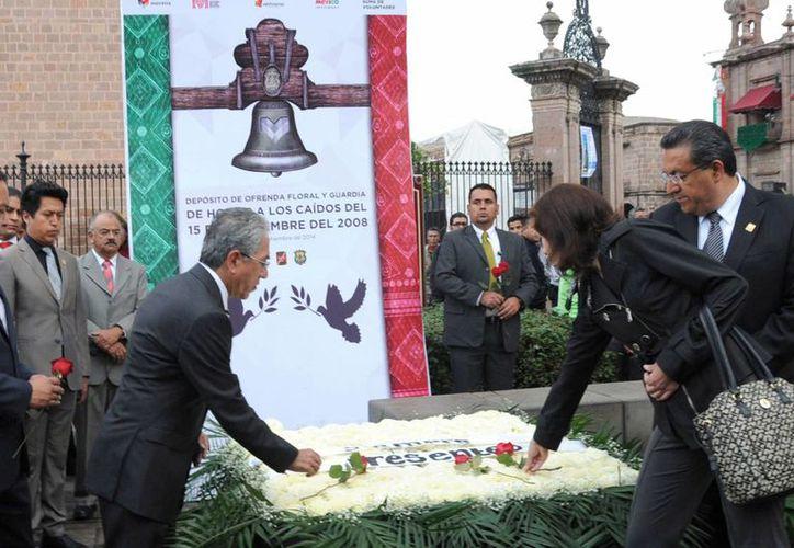 El día 15 de septiembre de 2008, granadazos arrebataron la vida de siete personas que asistían a la celebración del Grito de Independencia en el Zócalo de Morelia. En la imagen, autoridades colocan una ofrenda en memoria de las víctimas. (Archivo/Notimex)