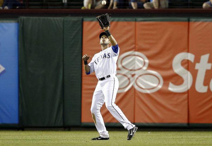 En esta foto de abril de este año, Alex Ríos, que entonces jugaba para Vigilantes de Texas, captura un elevado de Jayson Nix, de Filis de Filadelfia. (Foto: AP)