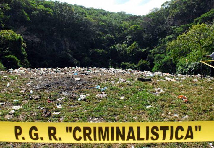 Análisis preliminares indican que los restos localizados en el basurero de Cocula no pertenecen a los cuerpos de alguno de los normalistas de Ayotzinapa. (Archivo/Notimex)