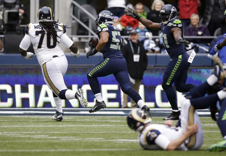 El linebacker Malcolm Smith, de los Seahawks de Seattle, segundo desde la izquierda, regresa una intercepción para touchdown contra los Rams de San Luis, en la primera mitad del juego. (Agencias)