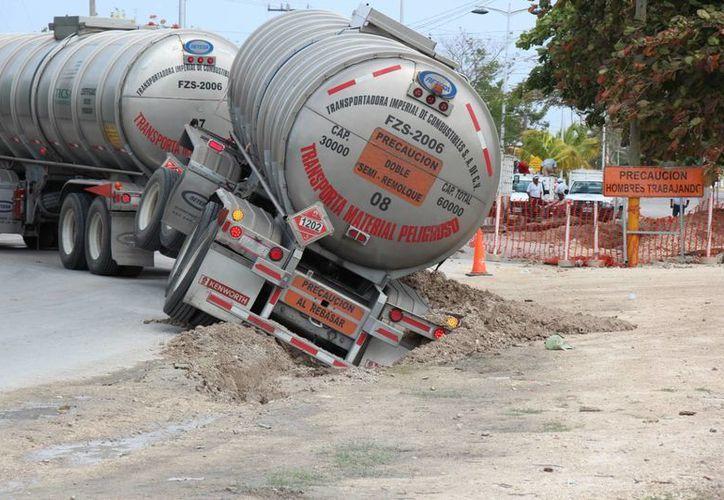 Un tráiler de doble remolque cayó en una zanja que quedó tras la instalación de tubería nueva de la CAPA. (Gustavo Villegas/SIPSE)