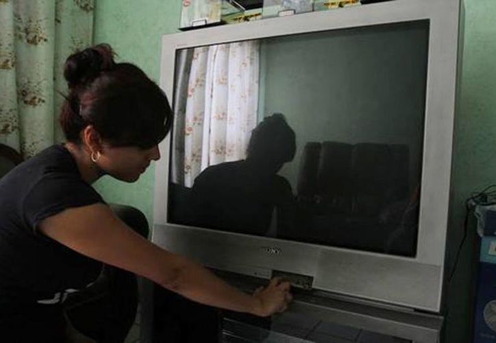 Tras apagón, la tv de paga retransmitirá los canales abiertos. Imagen de una mujer al encender un televisor. (Miguel Ángel González/Milenio)