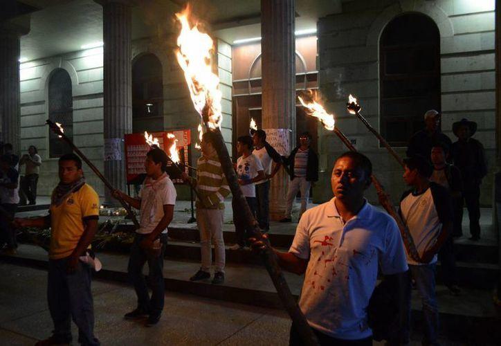 Normalistas hacen guardia con antorchas en Chilpancingo para exigir que sus compañeros aparezcan con vida. (EFE)