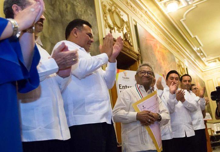 Armando Manzanero Canché sostiene el reconocimiento que acompaña la medalla 'Eligio Ancona', que ayer le fue entregada por el gobernador, Rolando Zapata  Bello. (Cortesía)