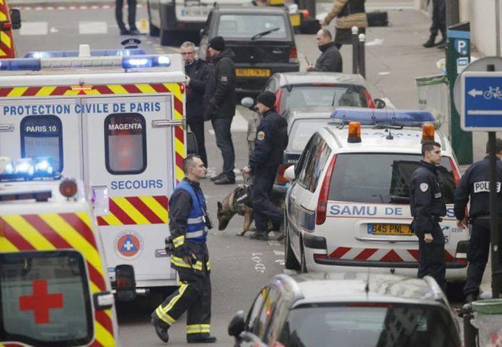 Policía y trabajadores de rescate patrullan la calle cerca de la oficina del periódico satírico francés Charlie Hebdo momentos después del atentado. (Archivo/Agencias)