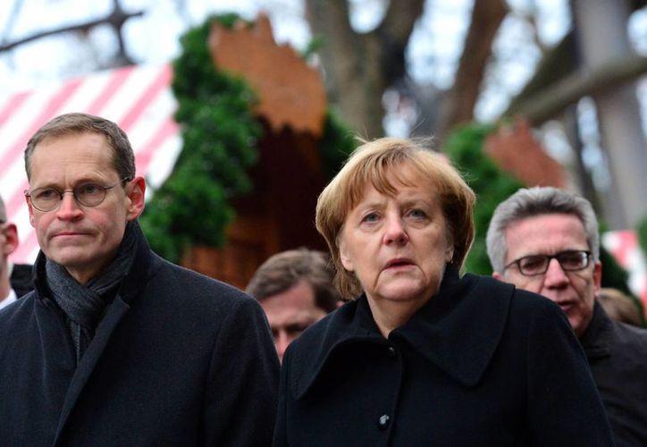 La canciller alemana Angela Merkel y el alcalde de Berlín, Michael Mueller, visitaron el lugar donde ocurrió el ataque. (Maurizio Gambarini/dpa vía AP)