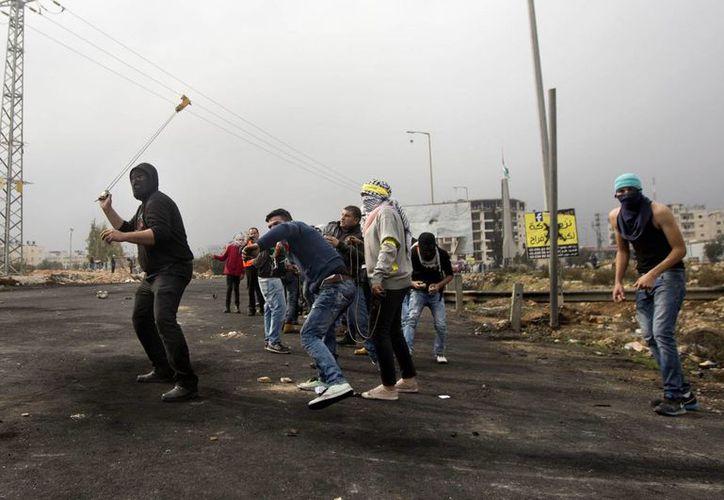Manifestantes palestinos arrojan piedras a soldados israelíes durante enfrentamientos en la ciudad de Ramala en Cisjordania. (Agencias)
