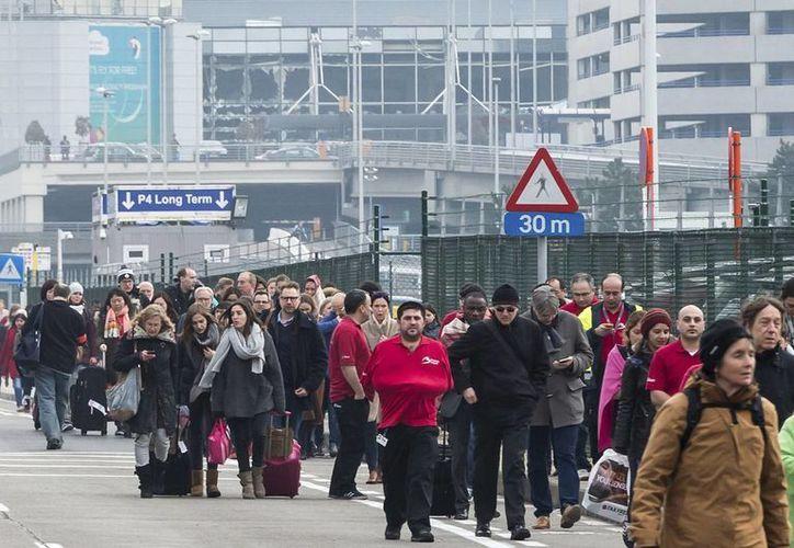 La gente camina lejos de las ventanas rotas en el aeropuerto de Zaventem en Bruselas después de una explosión este martes. Las explosiones sacudieron el aeropuerto de Bruselas y el Metro. (Foto AP / Geert Vanden Wijngaert)