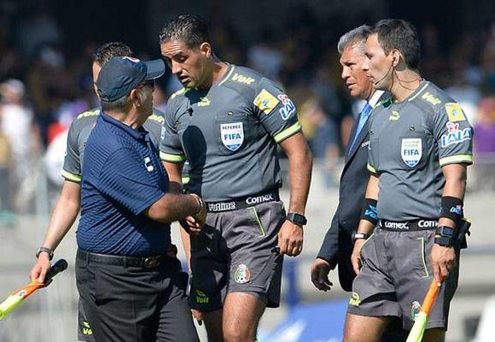 El técnico del Veracruz, Carlos Reynoso (izq) estrecha la mano con el silbante Roberto García Orozco, quien tuvo un mal trabajo en el partido de vuelta entre los Tiburones y los Pumas. (estoenlinea.oem.com)