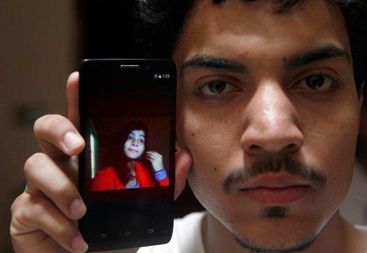 Hassan Khan enseña en su teléfono celular la foto de usu esposa Zeenat Rafiq, quien fue quemada viva por haberse casado contra las normas del matrimonio en ese país. (AP)