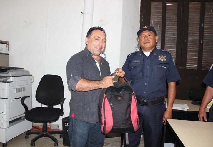 Andrés Ismael Santana Fraga, primer edil de Sotuta recuperó la mochila de manos del oficial, Edwin Ricardo Castillo Garrido. (Milenio Novedades)