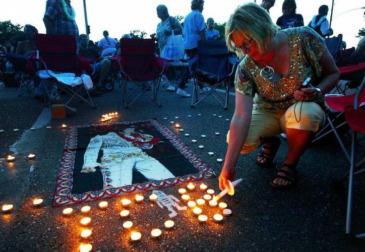 Una admiradora enciende una vela durante la vigilia en Graceland, la casa de Elvis Presley. (Agencias)