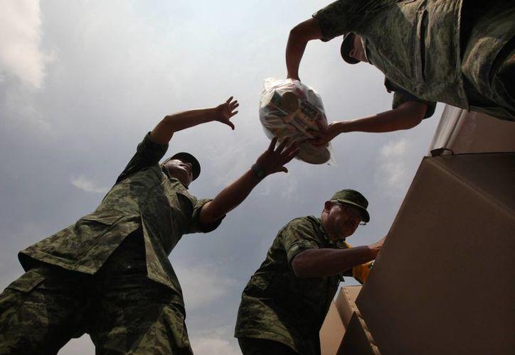 Soldados mexicanos transportan ayuda humanitaria para víctimas de 'Ingrid' y 'Manuel'. (Agencias)