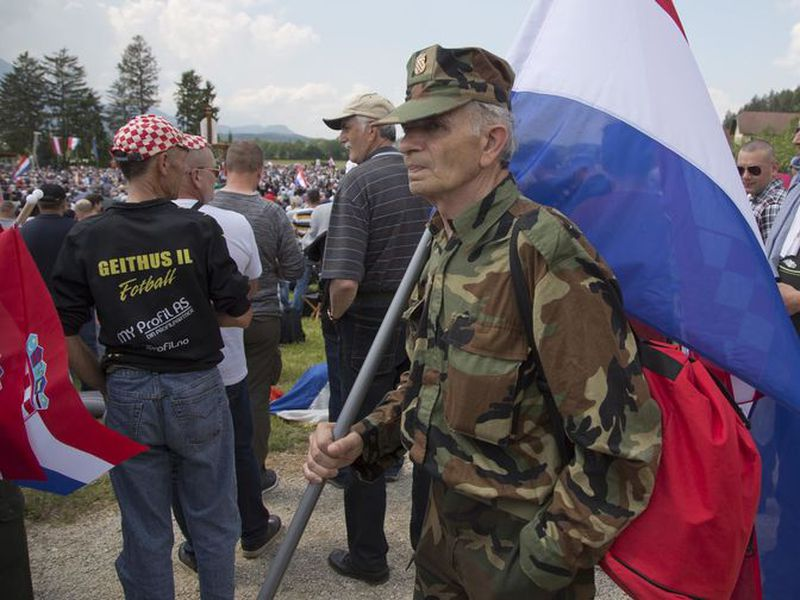 A uniformed man carries a Croatian flag during a commemoration ceremony in Bleiburg, Austria.