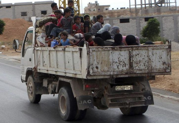 Un grupo de refugiados sirios se dirige a la frontera con Siria, cerca de la localidad libanesa de Arsal, en el valle de Bekaa, en Líbano. (EFE/Archivo)