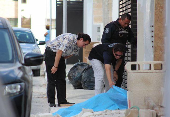 Los agentes ministeriales observan el cuerpo inerte del alarife, en el fraccionamiento Las Américas. (Aldo Pallote/Milenio Novedades)