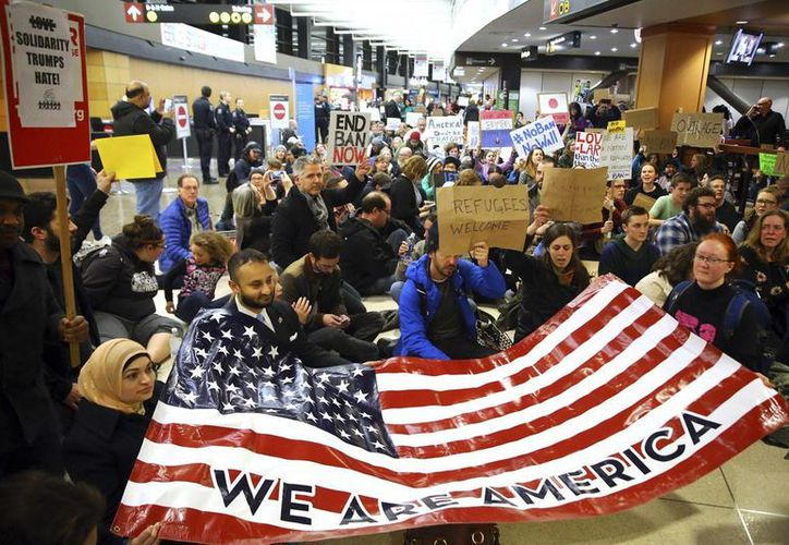 Imagen de un grupo de manifestantes en el vestíbulo de un aeropuerto con un letrero que dice 'Somos Estados Unidos'. (Genna Martin / seattlepi.com vía AP)
