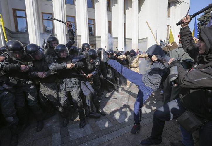 Activistas del movimiento radical ultranacionalista ucraniano se enfrentan a la policía ante el parlamento en Kiev, Ucrania. (EFE)