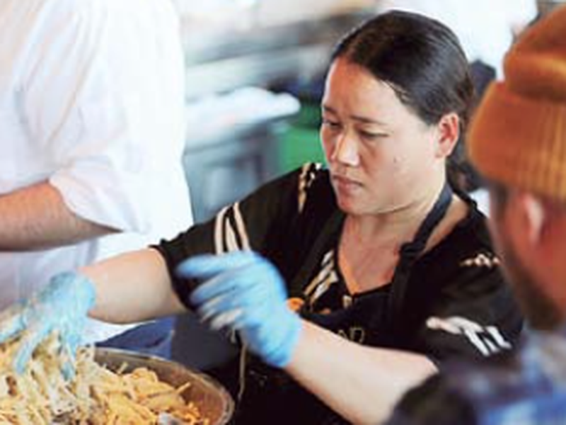 Pa Wah, a refugee from Myanmar, mixes shrimp in a turmeric tempura batter at the Hog Island Oyster Co. (AP)