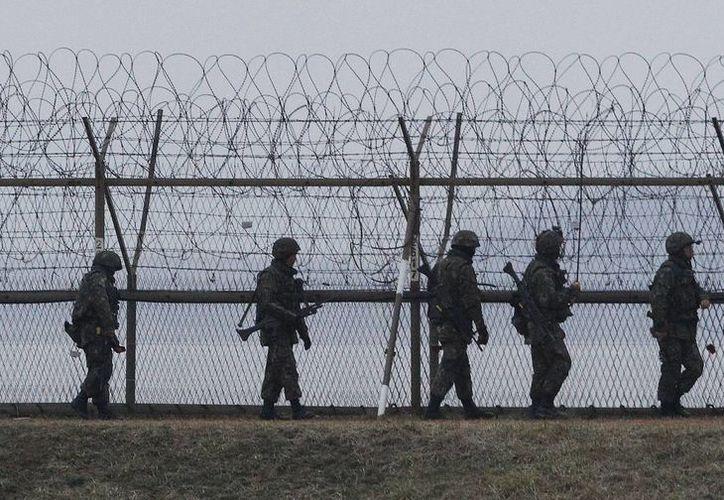 Soldados surcoreanos patrullan a lo largo de una cerca de alambre de púas, cerca de la localidad fronteriza de la Panmunjom, en Paju, Corea del Sur. (Agencias)