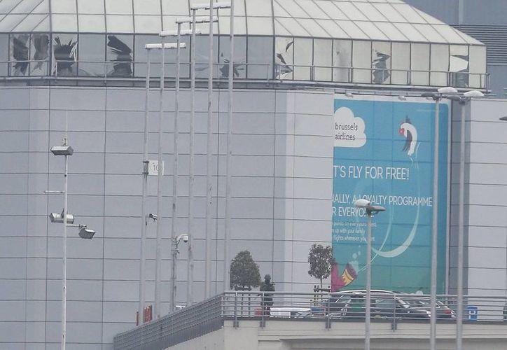 Un oficial de seguridad armado vigila delante de los cristales rotos de una fachada del aeropuerto internacional de Zaventem, cerca de Bruselas, Bélgica. (EFE/Archivo)