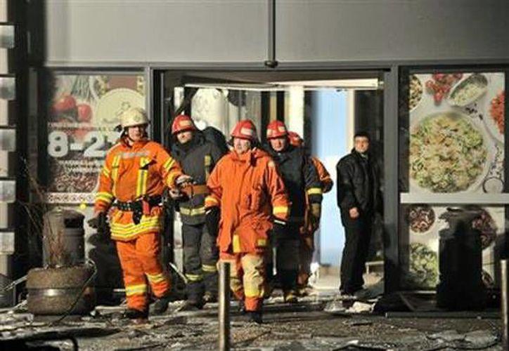 Socorristas salen del establecimiento donde se desplomo el techo. (Agencias)