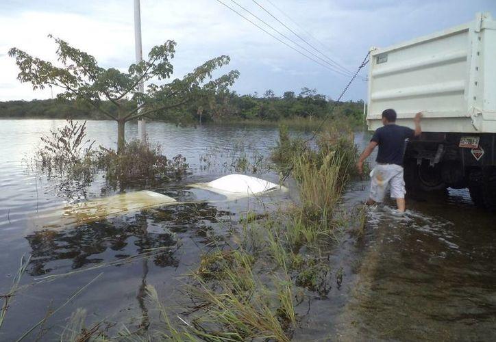 El vehículo se observó sumergido a un costado del camino. (Redacción/SIPSE)