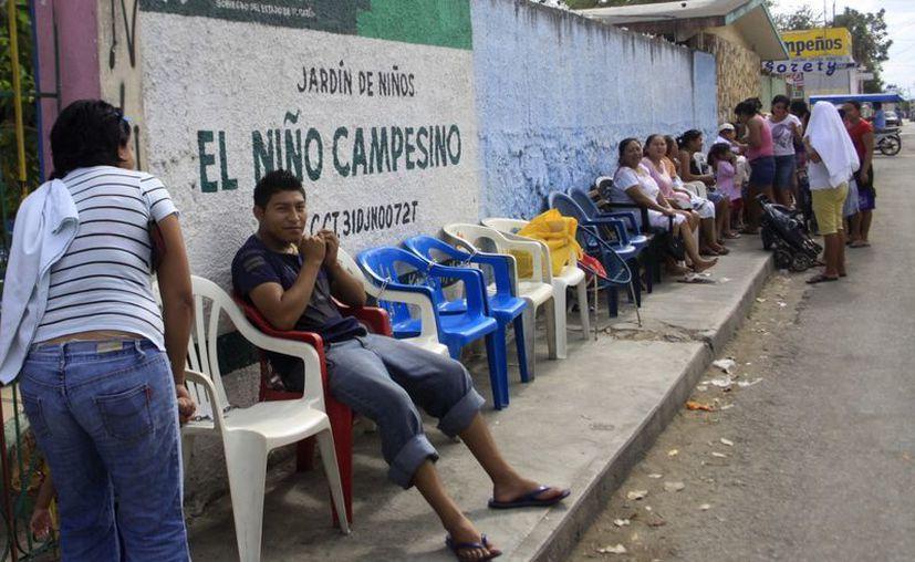 Desde el primer día de clases de 2013 hacen fila en busca de cupo para sus hijos. (Christian Ayala/SIPSE)