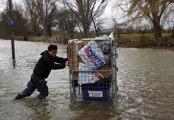 Un residente local empuja un carrito con algunas pertenencias en él en la parte inundada por las tormentas en el poblado Staines-upon-Thames, Inglaterra. (Agencias)