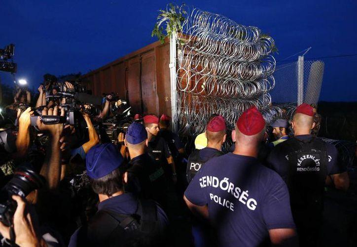 Policías húngaros resguardan las vías de tren cerca de Roszke, un importante punto de cruce fronterizo para migrantes, con la idea de cerrar un hueco clave en la valla fronteriza de 177 km que levantó el país. (Foto AP)
