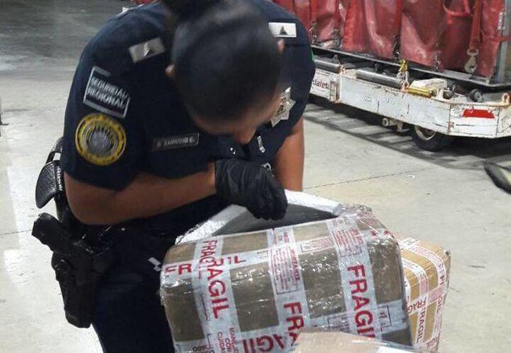 La policía aseguró varias cajas que contenían bolsos de mujer y maquillajes, en cajas de una empresa que no tenía los documentos de la legal procedencia de la mercancía. (Cortesía)