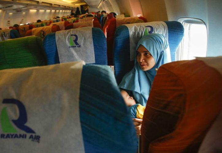 Imagen de una mujer musulmana como pasajera de un avión. Musulmanes denuncian discriminación religiosa para entrar a Estados Unidos. (AP)