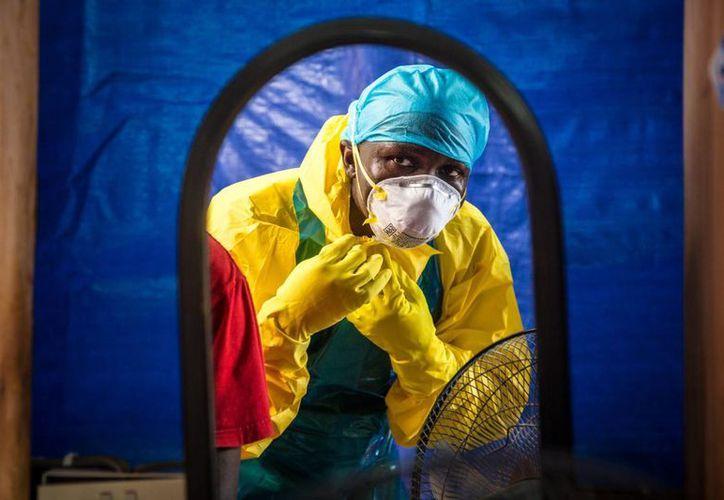 Un trabajador de salud se pone el equipo de protección antes de entrar en un centro de tratamiento de ébola en el oeste de Freetown, Sierra Leona, donde los casos del virus van en aumento. (Agencias)