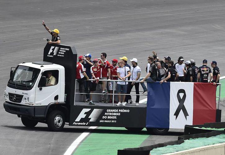 Los pilotos llevan un brazalete negro durante la vuelta de presentación en señal de luto por las víctimas de los atentados de París, un homenaje que la Federación Internacional del Automóvil (FIA) quiso dedicar también a los fallecidos en carretera, antes del Gran Premio de Formula Uno de Brasil. (EFE)