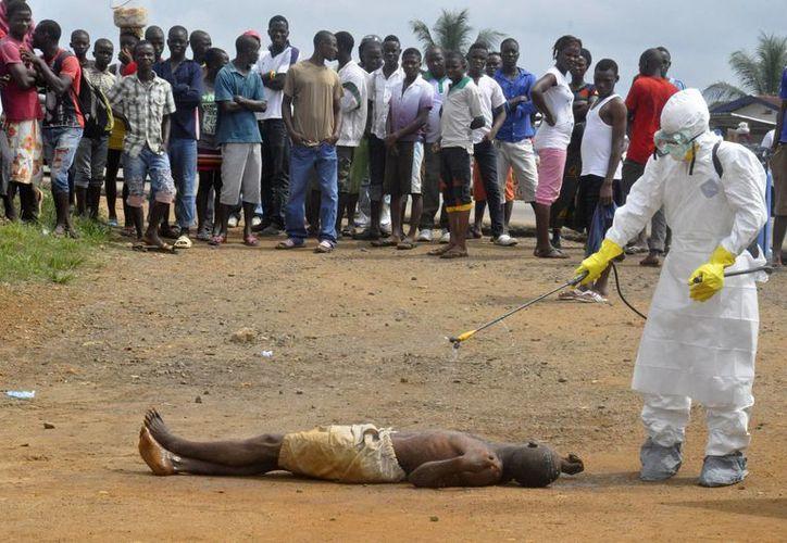 Un trabajador de salud rocía con desinfectante a un hombre que al parecer falleció por ébola, en Monrovia, Liberia. (Agencias)