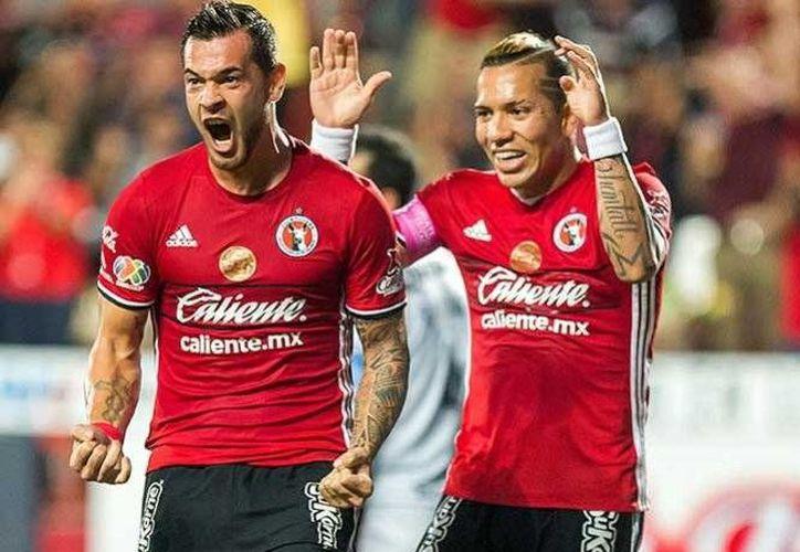 Milton Caraglio fue el responsable de darle las tres unidades a Xolos de Tijuana, quienes permanecen en el liderato de la Liga MX. En la foto, Caraglio(i) celebra con Dayro Moreno.(Foto tomada de Facebook/Xolos)